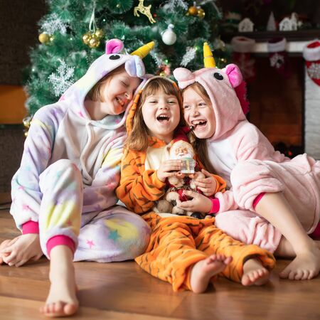 Happy little kids wearing kigurumi pajamas at Christmas eve. Three sisters in unicorn and tiger costumes siting in beautiful living room decorated for Xmas with traditional fire place..