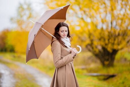 Attractive young elegant girl walking in the park with umbrella, autumn day, copyspace