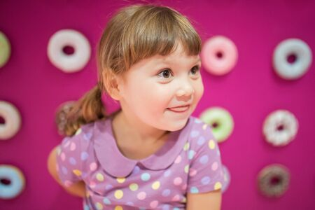 Cute little girl with colorful delicious donuts. Tasty food for kids. Child loving sweets