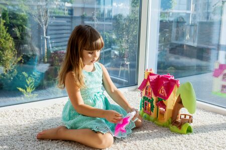 Adorable little girl playing with a dollhouse, sitting on the floor.