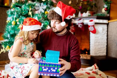 A happy family father and his little daughter open Christmas gifts together in beautiful living room decorated for Xmas. 版權商用圖片