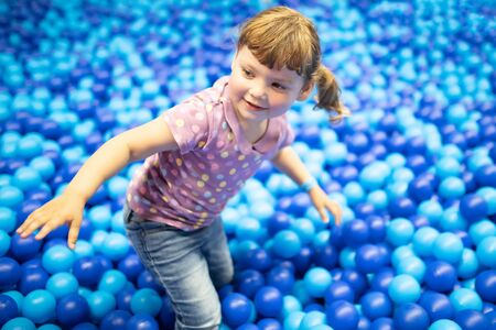 Happy little kid playing at colorful plastic balls playground high view. Adorable girl having fun indoors, kindergarten
