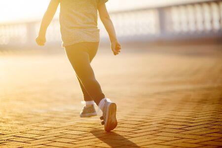 Little girl running down the street in the city at sunset, sport and avtivity for kids 版權商用圖片