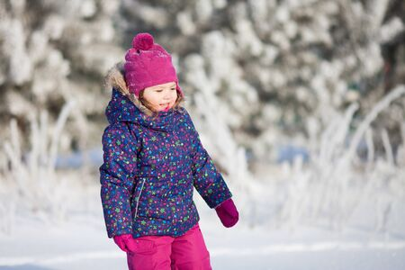 Cute toddler girl outdoors on a sunny winter day, having fun, snowy day Archivio Fotografico