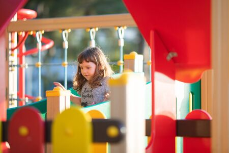 Cute happy little girl playing on outdoors playground