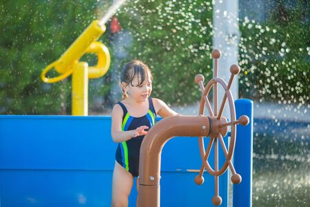 Little girl having fun playing with water in park at the water playground. Summer day