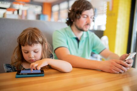 Little girl and her father playing on smartphones, spending day together. Addiction on devices
