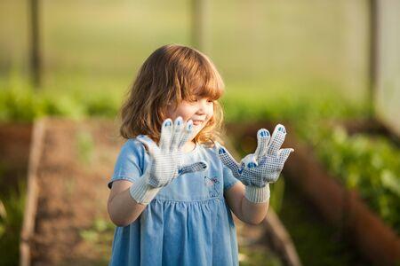 Adorable happy toddler girl in the greenhouse, wearing garden gloves, little gardener, mother's helper