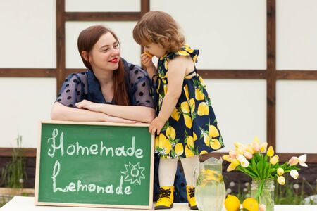 Happy family of mother and daughter having fun selling lemonade outdoors, sunny summer day