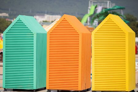 Row of brightly colored wooden cabanas by the seaside