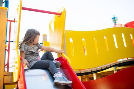Cute happy little girl at children's slide on a playground or kindergarten 版權商用圖片