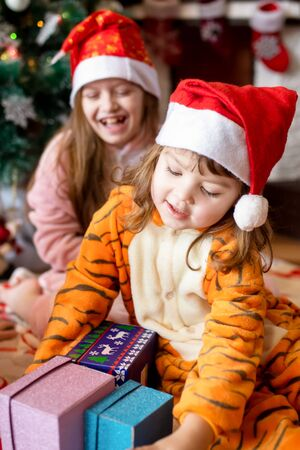 Happy little kids wearing kigurumi pajamas at Christmas eve. Two sisters in unicorn and tiger costumes opening presents in beautiful living room decorated for Xmas with traditional fire place..