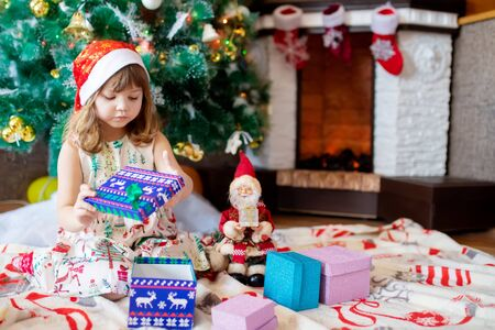 Adorable little girl opening her christmas presents beside a christmas tree Archivio Fotografico