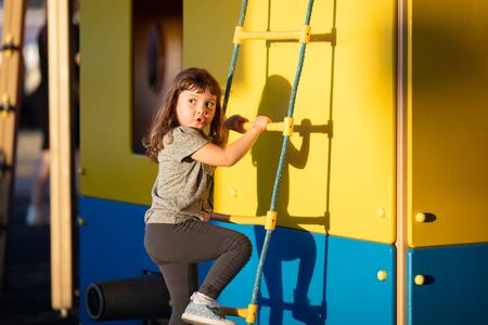 Cute happy little girl playing, climbing on outdoors playground