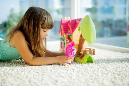 Adorable little girl playing with a dollhouse, sitting on the floor. Archivio Fotografico