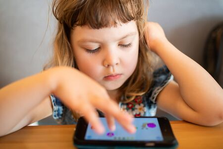 Little girl playing on her smartphone with a serious thoughtful face