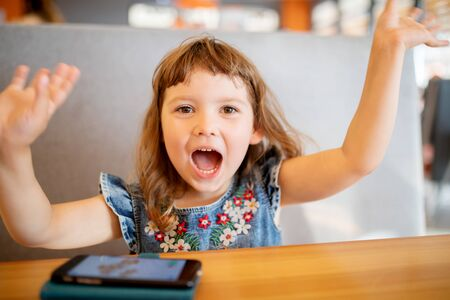 Little girl is very happy to play on her smartphone Archivio Fotografico