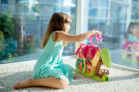 Adorable little girl playing with a dollhouse, sitting on the floor. Banque d'images