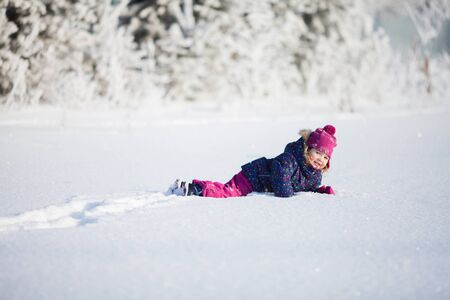Cute toddler girl playing outdoors on a sunny winter day Archivio Fotografico