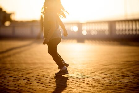 Little girl running down the street in the city at sunset, sport and avtivity for kids Archivio Fotografico