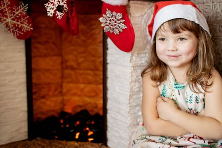 Adorable smiling little girl wearing Santa hat in beautiful living room decorated for Xmas with traditional fire place. Copy space 版權商用圖片