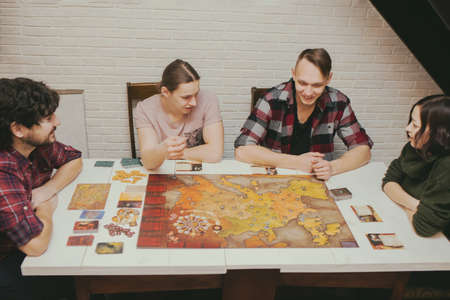 Group of friends sitting at the table. Young People having fun while playing board game.