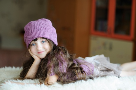 Adorable toddler girl in purple hat is lying on white fur  Stock Photo