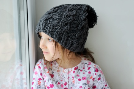 Adorable kid girl with big eyes in dark grey knit hat near the window  Stock Photo