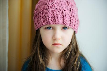 fille triste: Close-up portrait d'une jeune fille enfant portant bonnet tricoté rose Banque d'images