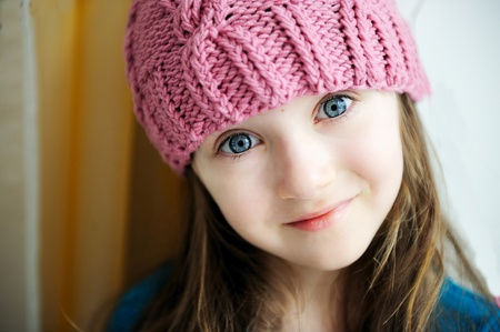 pink hat: Close-up portrait of a child girl wearing pink knitted hat