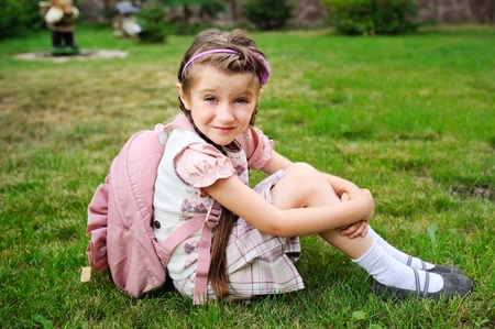 Young school girl with pink backpack sits on grass