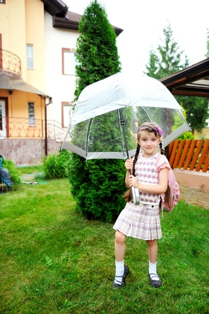 Brunette schoolgirl with backpack under umbrella on a rainy day photo