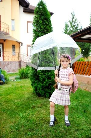 schoolgirl uniform: Brunette schoolgirl with backpack under umbrella on a rainy day Stock Photo