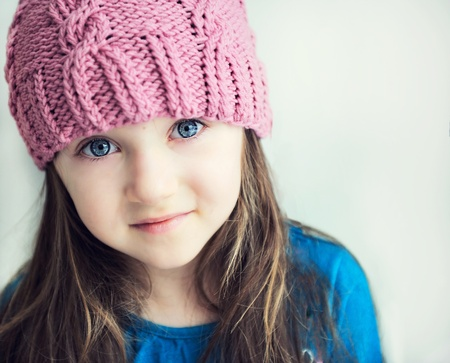 Close-up portrait of a child girl wearing pink knitted hat photo