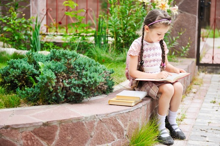 Young school girl with pink backpack sits reading the book photo