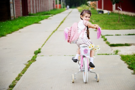 Young school girl with backpack rides her pink bike to school photo