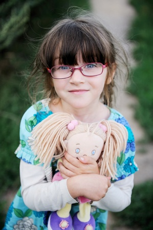 Adorable brunette child girl in glasses hugs her baby doll photo