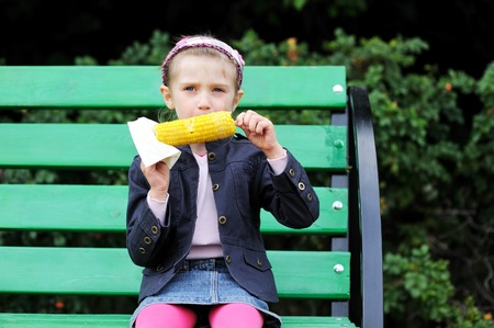 Pretty child girl eating a boiled corn outdoors