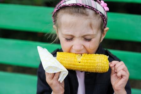 meisje eten: Pretty kind meisje het eten van een gekookte maïs buiten