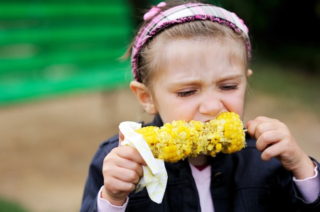 elote: Niña bonita comer una al aire libre de maíz hervida
