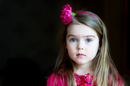 Cute child girl with flower headband on a dark background