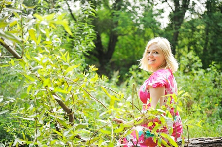 Outdoors portrait of beautiful blond woman in flower dress sitting on a log in the forest photo