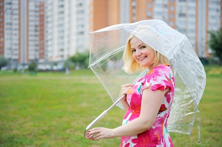 Portrait of adorable blond woman in flower dress posing outdoors with umbrella photo