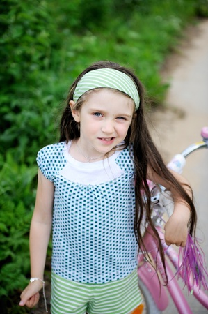 loose hair: Beautiful long-haired child girl outdoors with pink bicycle