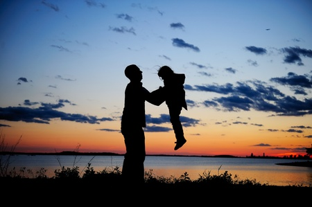 Silhouette of father lifting up a daughter in the sunset photo