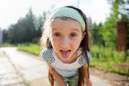 protrude: Outdoors portrait of amazed child girl with protruding tongue Stock Photo