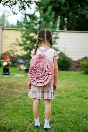 Young school girl with pink backpack poses outdoors photo