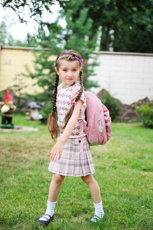 satchel: Young school girl with pink backpack poses outdoors