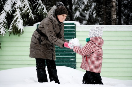 family fight: Young mother and her adorable daughter play snowball on a bright winter day Stock Photo