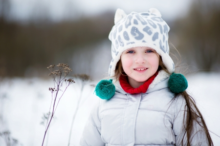 Winter portrait of adorable happy child girl in warm clothes photo